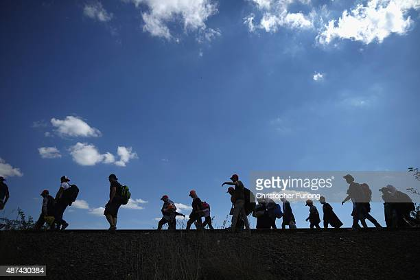 Migrants cross into Hungary as they walk over railroad tracks at the Serbian border with Hungary at dusk on September 9 2015 in Roszke Hungary...