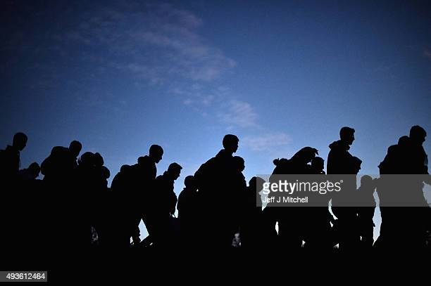 Migrants cross into Slovenia at night on October 21 2015 near the village of Dobova Slovenia Migrants are escorted by police and soldiers after...