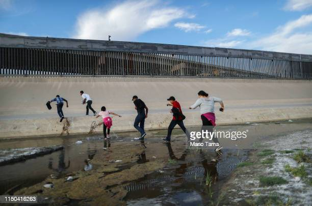 Migrants cross the border between the US and Mexico at the Rio Grande river as they enter El Paso Texas on May 19 2019 as taken from Ciudad Juarez...