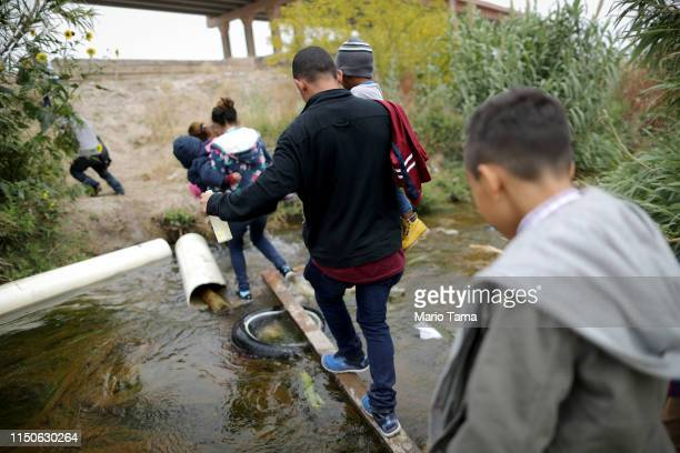 Migrants cross the border between the US and Mexico at the Rio Grande river as they enter El Paso Texas on May 20 2019 as taken from Ciudad Juarez...
