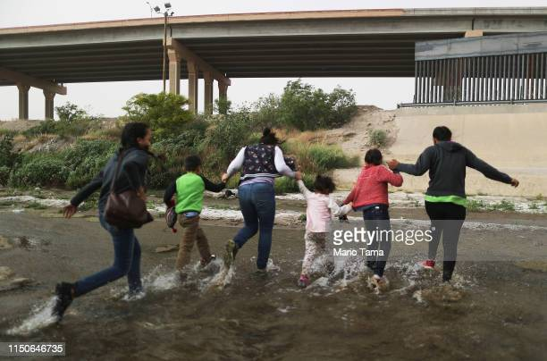 Migrants cross the border between the U.S. And Mexico at the Rio Grande river, as they enter El Paso, Texas, on May 20, 2019 as taken from Ciudad...