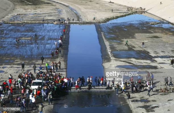 Migrants cross the nearly dry Tijuana River as they make their way around a police blockade toward the El Chaparral port of entry on November 25 2018...