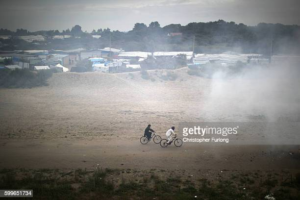 Migrants cycle through smoke from a fire burning rubbish at the Jungle migrant camp on September 6 2016 in Calais France The dropin cafe for children...