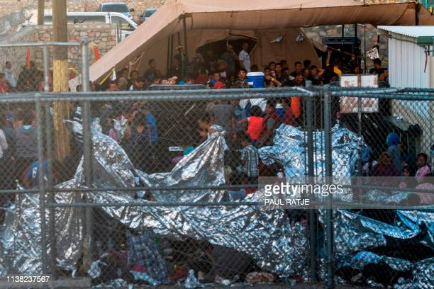 Migrants detained by US Customs and Border Protection are pictured in a makeshift holding facility beneath Paso Del Norte bridge between downtown El...