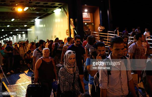 Migrants disembark along with European tourists from a Blue Star ferry on the Greek mainland port of Piraeus near Athens after a 10 hour ferry ride...
