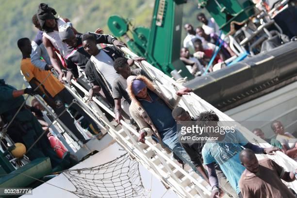 Migrants disembark from the Spanish Guardia Civil Rio Segura Patrol Ship with 1216 migrants onboard including 256 children and 11 pregnant women who...