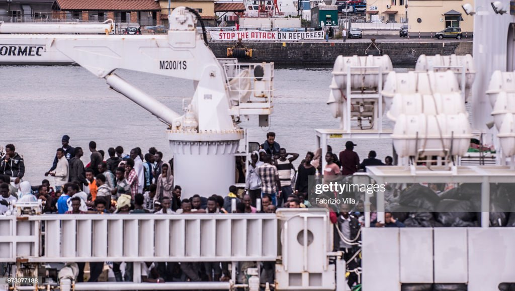 Migrants disembark the Italy's coastguard ship Diciotti at the port of Catania. âStop the attak on refugeesâ: a banner of several demonstrators in support of migrants,on June 13, 2018 in Catania, Italy. The Diciotti ship carried 932 migrants rescued in Mediterranean Sea in the last days, and two bodies. Among the rescued people there were children and 13 pregnant women. The Italian interior Minister, Matteo Salvini said on Sunday that all Italian ports were closed to the rescue boat Aquarius chartered by Sos Mediterranee.