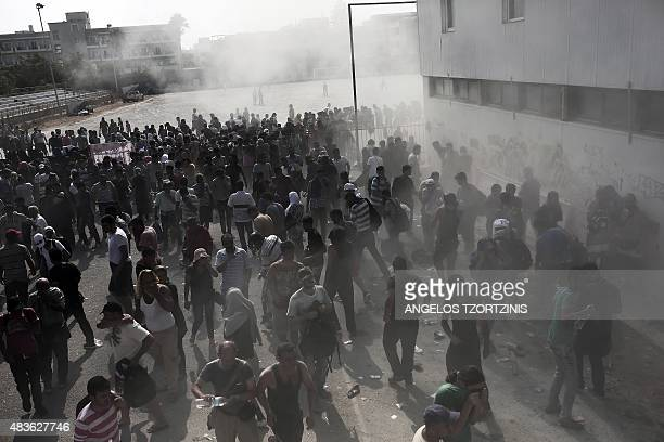 Migrants disperse after policemen sprayed them with fire extinguishers during a gathering for a registration procedure at the stadium on the Greek...