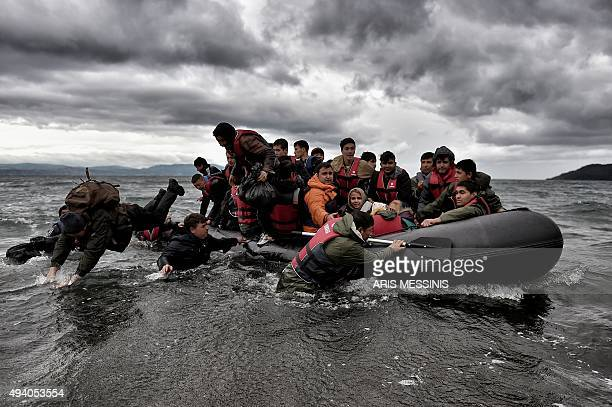 Migrants dive into the sea to help other refugees and migrants to land on the Greek island of Lesbos on October 24 after crossing the Aegean sea from...