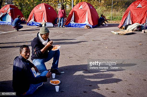 Migrants eat a plateful of pasta offered by volunteers at the tent city for migrants in transit , by the volunteers of Baobab Experience and Doctors...