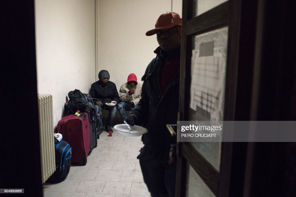 Migrants eat food donated by a charity organisation at the train station in Bardonecchia on January 13, 2018. Migrants are now trying to reach France crossing the Italian Alps by the snow-covered pass Colle della Scala (Col de l'Echelle) despite snow and bad weather conditions. / AFP PHOTO / Piero CRUCIATTI