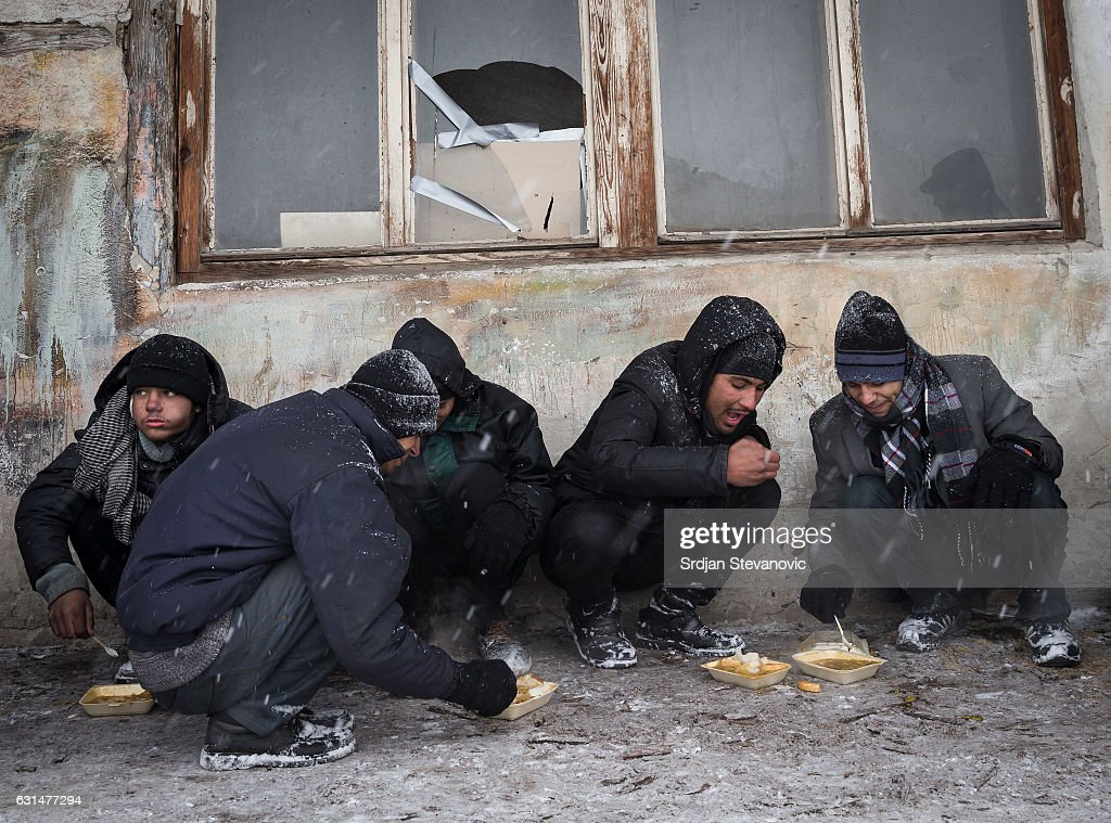 A migrants eats a plate of free food as snow falls outside a derelict customs warehouse on January 11, 2017 in Belgrade, Serbia. It is estimated that around 1, 000 migrants are sleeping rough in Serbia, enduring temperatures as low as 20 degrees celcius.