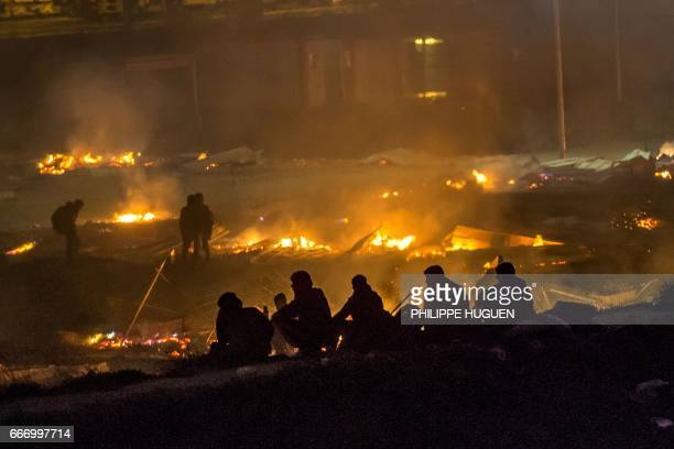 Migrants evacuate as a huge fire blazes through the GrandeSynthe migrant camp outside the northern French city of Dunkirk late April 10 reducing it...