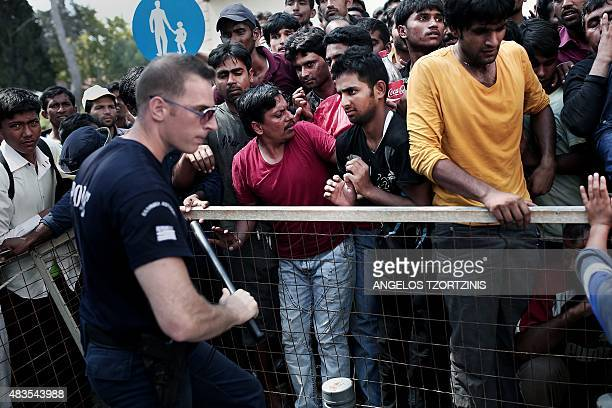 Migrants face a policeman as they wait behind a fence to be registered by the police outside a police station on the island of Kos on August 10 2015...
