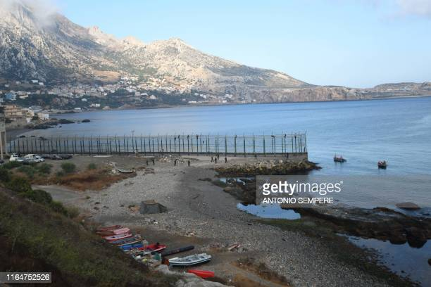 Migrants force their way into the Spanish territory of Ceuta on August 30, 2019. Over 150 migrants made their way into Ceuta after storming a...