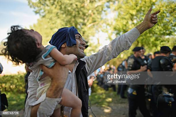 Migrants force their way through police lines at Tovarnik station to board a train bound for Zagreb on September 17 2015 in Tovarnik Croatia Migrants...