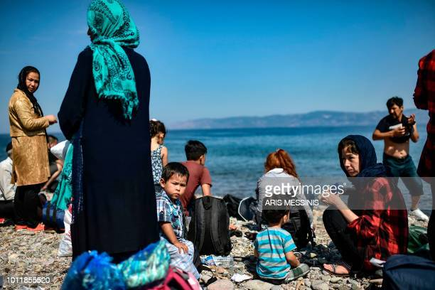 TOPSHOT Migrants from Afghanistan arrive after crossing the Aegean Sea from Turkey with a dinghy on the Greek Mediterranean island of Lesbos on...