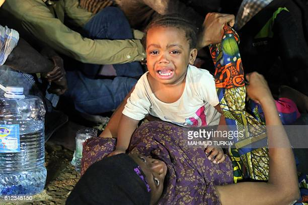Migrants from African origin wait at the port in the Libyan town of Garabulli east of Tripoli on October 3 2016 after they were rescued by the Libyan...
