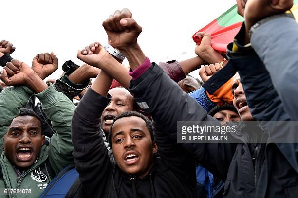 Migrants from Ethiopia cross their arms to symbolise the protest of the Ethiopian Oromo community against the government as they celebrate leaving...