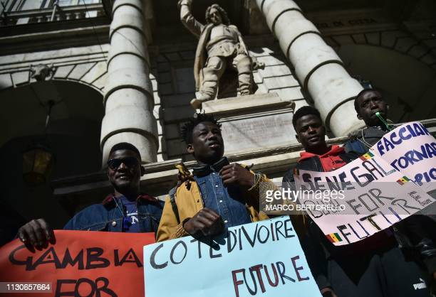 Migrants from Gambia and Senegal take part in a protest against global warming in central Turin on March 15, 2019.