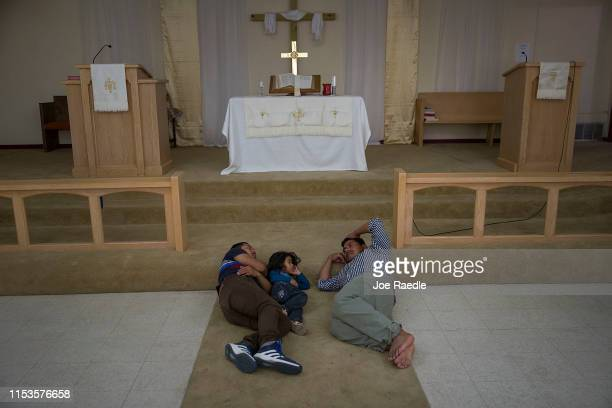 Migrants from Guatemala rest near the altar at the El Calvario Methodist Church which is housing migrants who are seeking asylum after being released...