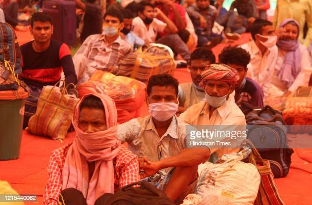 Migrants from Jharkhand wait underneath a tent at Tau Devi Lal Stadium for transit buses to Faridabad where they were to board a Shramik Special...
