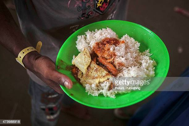 Migrants from Myanmar eat at camp shelters in the fishing port of Kuala Langsa in Aceh province on May 19 2015 in Kuala Langsa Indonesia Hundreds of...