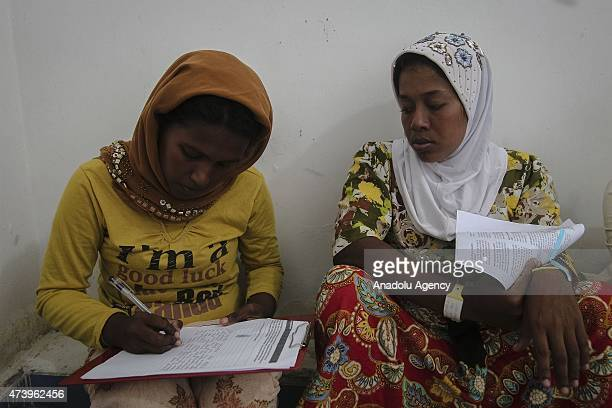 Migrants from Myanmar fill the personal data sheet to be registered with UNHCR at the camp shelters in the fishing port of Kuala Langsa in Aceh...