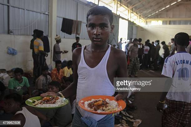 Migrants from Myanmar have lunch at the camp shelters in the fishing port of Kuala Langsa in Aceh province May 19 2015 Hundreds of migrants from...