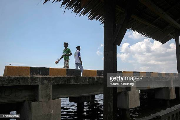 Migrants from Myanmar seen walking on the bridge outsider their camp shelters in the fishing port of Kuala Langsa in Aceh province on May 19 2015 in...