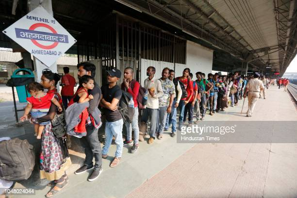 Migrants from North Indian states of Uttar Pradesh and Bihar stand in queue to board a train to Agra as they are returning home from Gujarat...