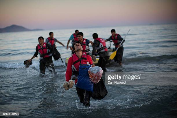 Migrants from Pakistan land on shore after completing a journey in a small dinghy crossing a three mile stretch of the Aegean Sea from Turkey August...