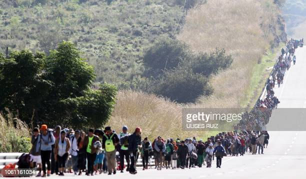 TOPSHOT Migrants from poor Central American countries mostly Hondurans moving towards the United States in hopes of a better life walk along the road...