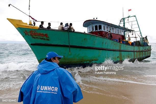 Migrants from Sri Lanka remain on their boat despite their vessel being washed ashore on the west coast of Lhoknga on June 14 2016 in Aceh Besar...