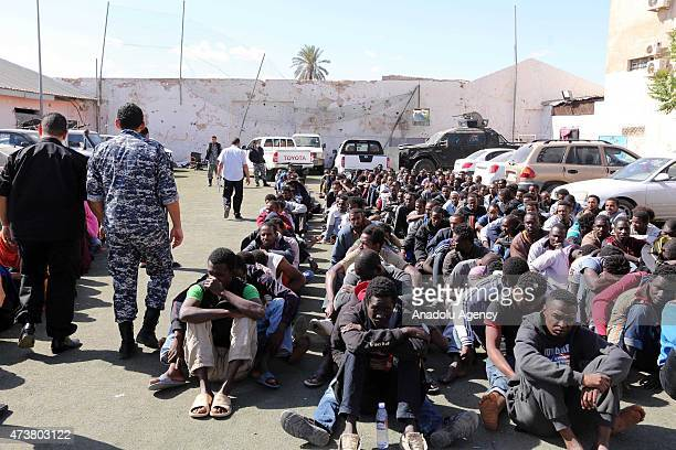 Migrants from subSaharan Africa sit waiting at a detention center on May 17 2015 in the capital Tripoli after they were arrested in Tajoura east of...