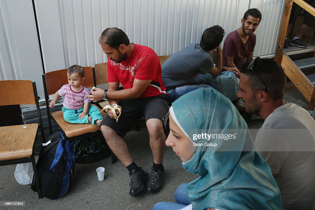 Migrants from Syria wait to be taken to a migrants' shelter after they completed the registration process at a facility of the German Federal Police (Bundespolizei) on September 1, 2015 in Deggendorf, Germany. Trains from Budapest have brought over 1,000 migrants to Germany in the last 24 hours, though the flow abated quickly after Hungarian authorities prohibited migrants from boarding further trains at Budapest's Keleti station this morning. Up to 1,600 migrants are currently arriving in Bavaria in southern Germany a day and will seek asylum. Germany is expecting to receive 800,000 asylum-seeking migrants this year and is struggling to cope with the record number.