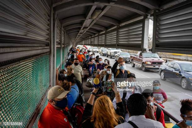 Migrants from the Matamoros camp cross the border bridge into the United States in Matamoros, Tamaulipas state, Mexico, on Friday, Feb. 26, 2021....