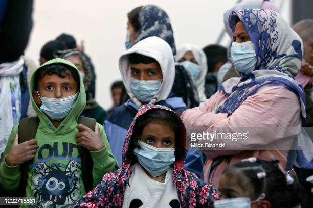 Migrants from the Moria camp in Lesbos island wearing masks to prevent the spread of the coronavirus wait for a bus after their arrival at the port...