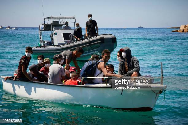 Migrants from Tunisia dock their boat at a port on August 28, 2020 in Lampedusa, Italy. Lampedusa, which is at the forefront the EU's struggle to...