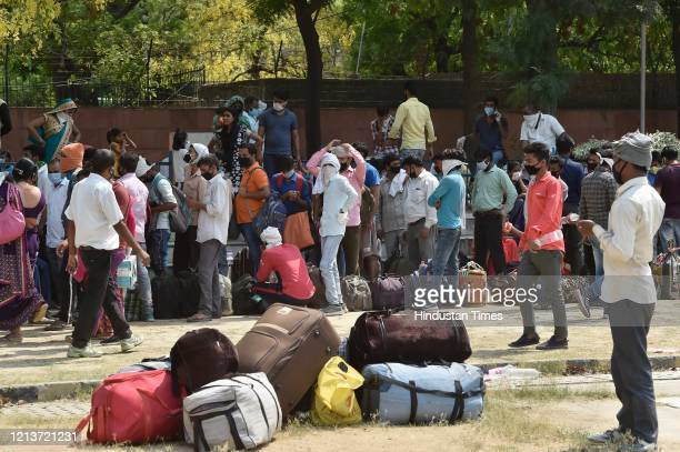 Migrants from various states wait to register for transport services being provided by the Delhi government at Delhi Pharmaceutical Sciences and...