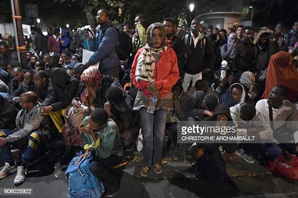 TOPSHOT Migrants gather and wait before being evacuated from a makeshift migrant camp set up between the metro stations of Jaures and Stalingrad in...
