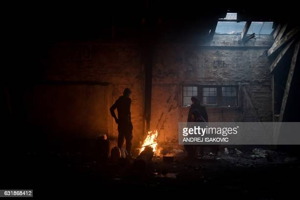 Migrants gather around a bonfire inside of derelict warehouse used as a shelter near Belgrade's main railway station on January 17 with temperatures...
