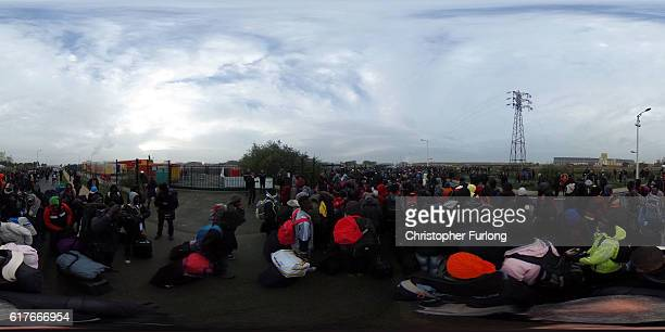 Migrants gather as they begin to leave the Jungle camp before authorities demolish the site on October 24 2016 in Calais France Police and officials...