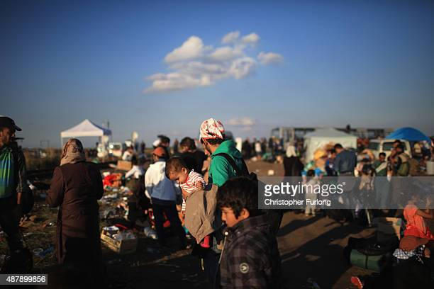 Migrants gather in a holding area to get waiting buses to take them to a migrant camp at the Hungarian border with Serbia on September 12 2015 in...