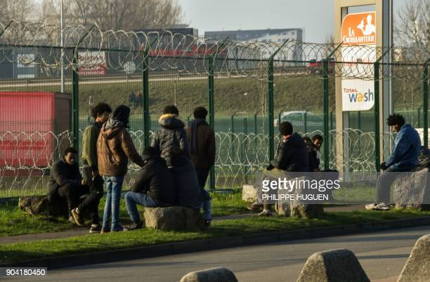 Migrants gather near the barbed wire fence of a truck parking lot near the N216 highway that leads to the ferry terminal on January 12 2018 in Calais...