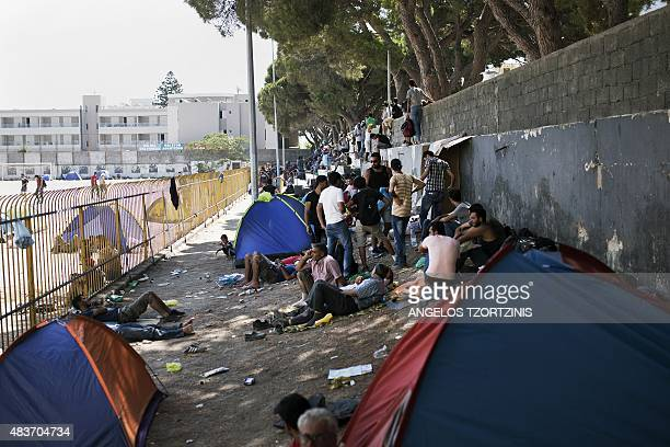 Migrants gather outside the stadium where they go through a registration procedure by the police on the Greek island of Kos on August 12 2015 The...