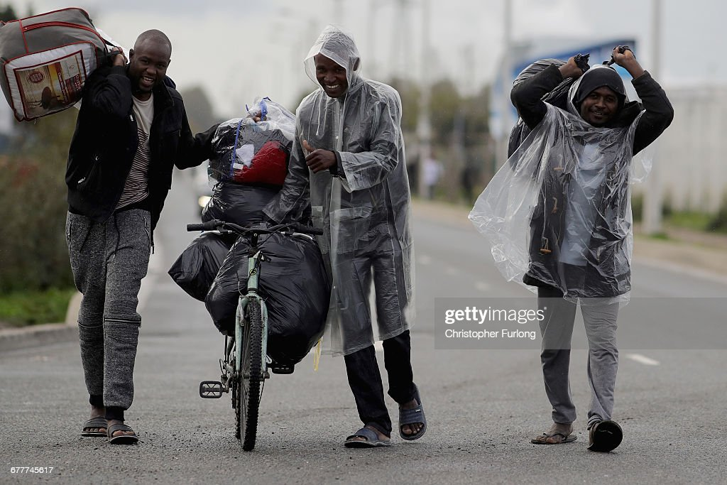 migrants gather their belongings as they prepare to leave the jungle