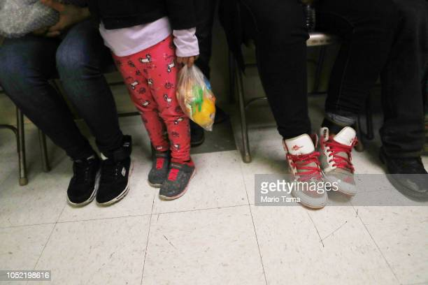 Migrants gather with their belongings as they are received at an Annunciation House shelter for migrants on October 12 2018 in El Paso Texas...
