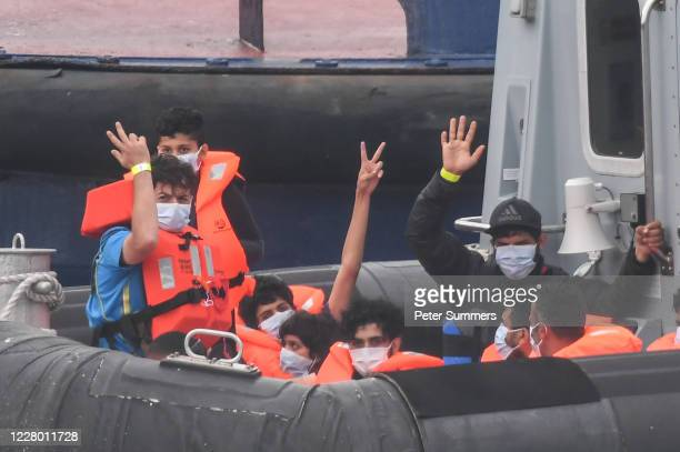 Migrants gesture as they arrive in port aboard a Border Force vessel after being intercepted while crossing the English Channel from France in small...