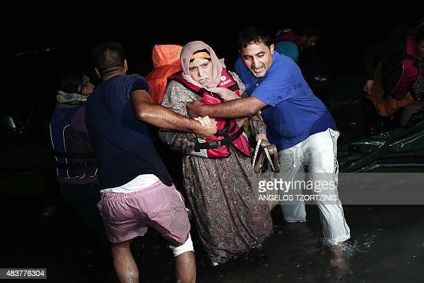 Migrants get out of an inflatable boat as they arrive on the Greek island of Kos after crossing a part of the Aegean Sea between Turkey and Greece on...